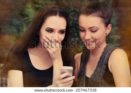 Young Women Surprised by Text Message - Two girls look surprised by something on the smart phone screen.   - stock photo