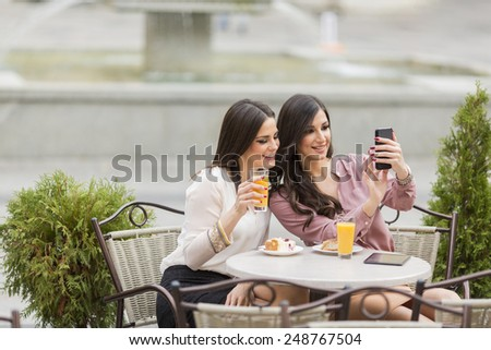 Young women taking photo with cellphone in the cafe