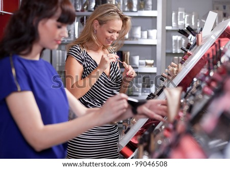 Young women testing and buying powder in a beauty store - stock photo