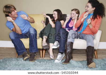 Young women throwing popcorn at male friend on sofa - stock photo