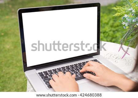 Young women using laptop computer on table at garden . view side. mock up screen free space for your design - stock photo