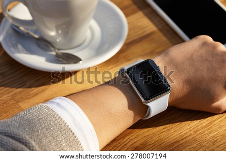 Young women wears smart watch and drinks coffee - stock photo