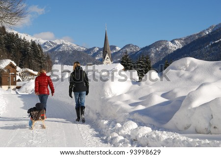 Young women with baby in sleigh walking in snow covered landscape in austria.