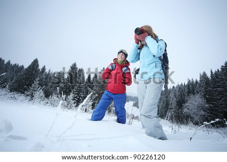 Young women with backpacks standing in a snowy field. One is smiling another one taking shoot with a camera. - stock photo