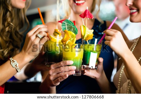 Young women with cocktails in bar or club - stock photo