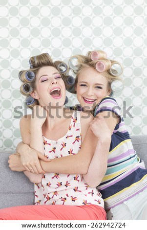 Young women with curlers, laughing