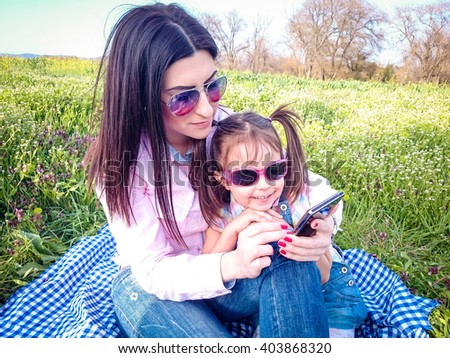 Young women with daughter on the phone on a sunny day outdoors