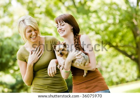 Young women with dog walking in a park - stock photo