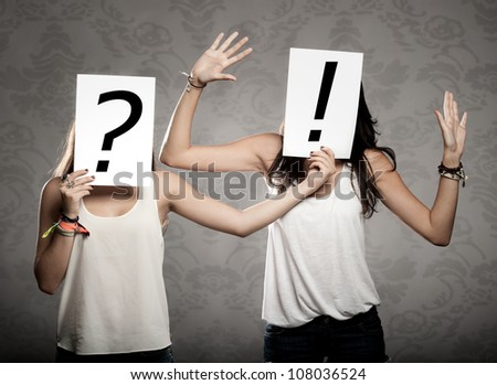 young women with interrogation and exclamation symbols in front of their faces - stock photo