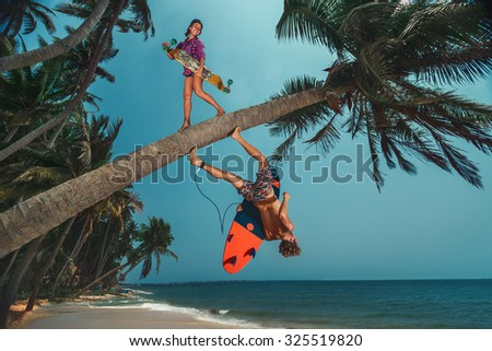 Young women with longboard and men with surfboard on coconut palm on beach. - stock photo