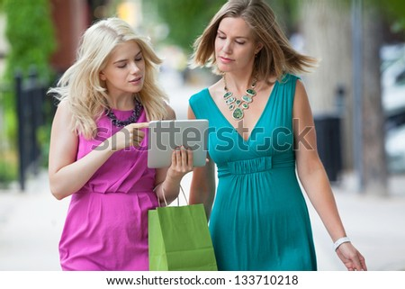 Young women with shopping bag using digital tablet