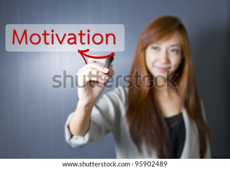 Young women write Motivation word. - stock photo