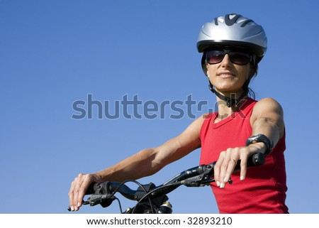Young womnem with helmet cycling isolated on blue sky - stock photo