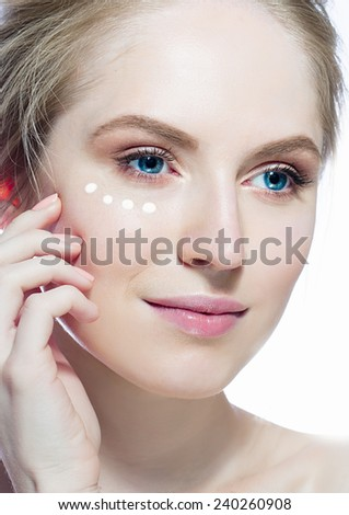 Young wonderful woman applying cream drops  on her face, blond hair and blue eyes - stock photo