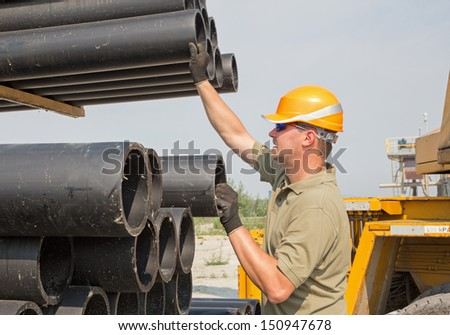 young worker and plastic pipes