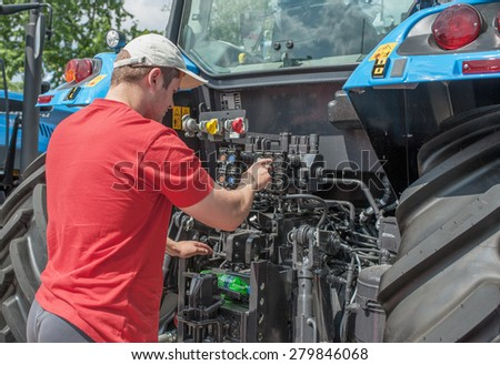 young worker checks the pressure of the engine - stock photo