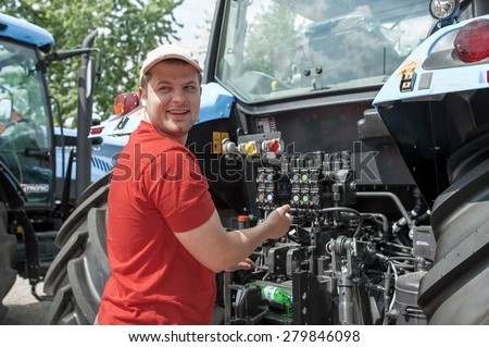 young worker checks the pressure of the tractor engine  - stock photo