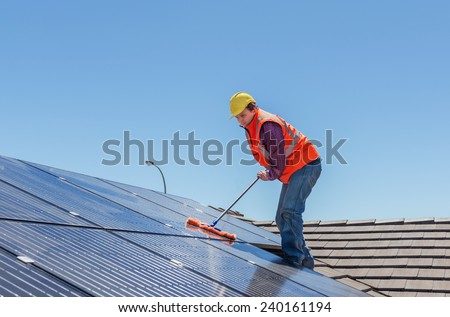 young worker cleaning solar panels on house roof - stock photo