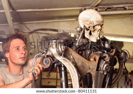 Young worker finishing his robot - stock photo