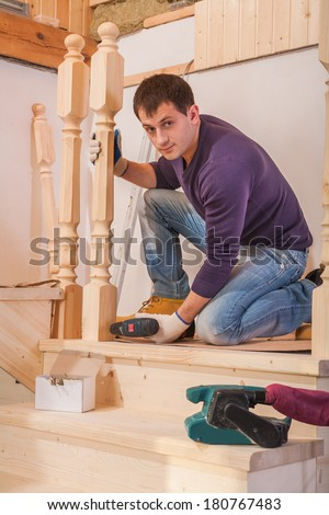 young worker fixing post of wooden  ladder and looking at camera