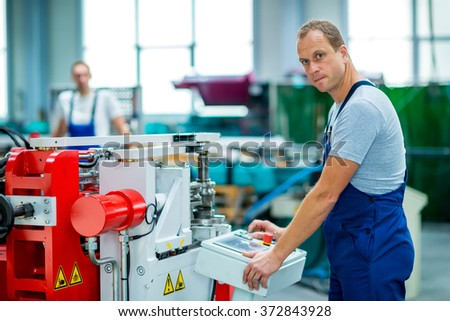 young worker in factory using machine - stock photo
