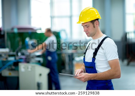 young worker in factory using tablet pc - stock photo