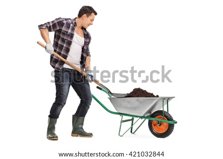 Young worker loading dirt into a wheelbarrow with a shovel isolated on white background - stock photo