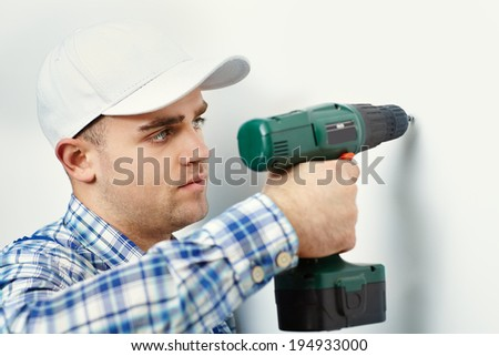 Young worker man with electric drill making hole in white wall