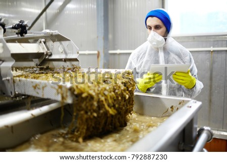 Young worker of seafood processing plant controling process of seaweed salad preparation