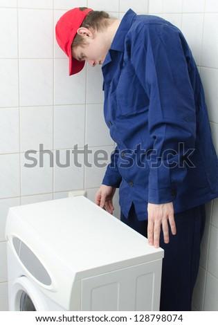 Young worker repairing washing machine - stock photo