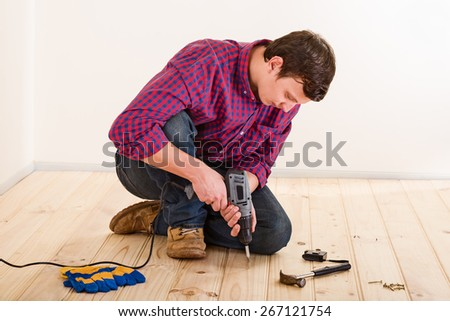 Young worker with screwdriver installing wooden flooring in the room - stock photo