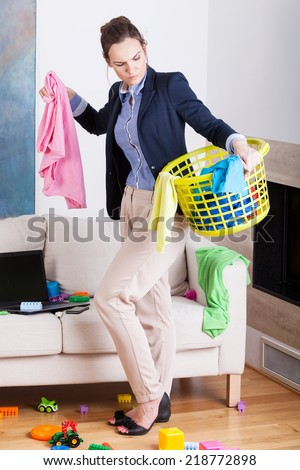 Young working mother collecting clothes for laundry  - stock photo