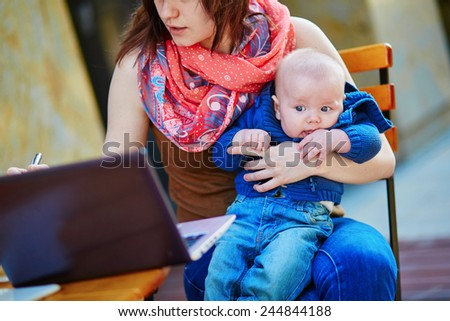 Young working mother with her little son in a cafe - stock photo