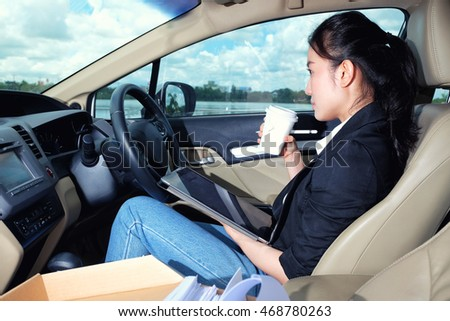 Young working woman using digital tablet in the car