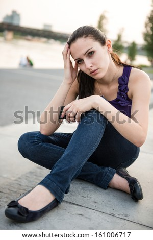 Young worried and nervous woman holding mobile phone