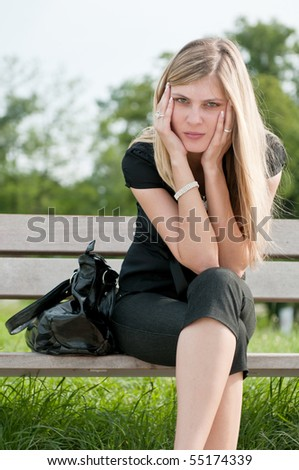 Young worried beautiful woman siting on bench - head in hands - stock photo