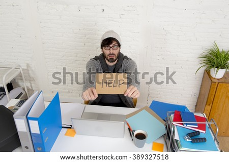young worried businessman in cool hipster beanie look holding help sign working in stress at home office with computer in business frustration overworked and deadline project - stock photo