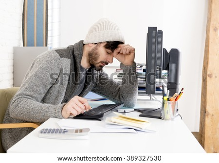 young worried businessman in cool hipster beanie look looking desperate having problem working in stress at home office with computer in business frustration overworked and deadline project - stock photo