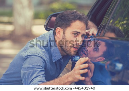 Young worried funny looking man obsessing about cleanliness of his new car. Car care and protection concept   - stock photo