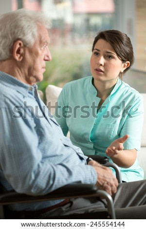 Young worried nurse talking with with older man - stock photo