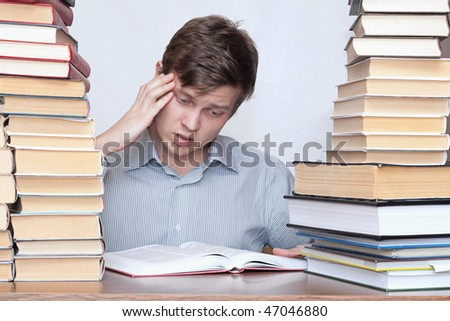 Young worried student reading philosophy between books