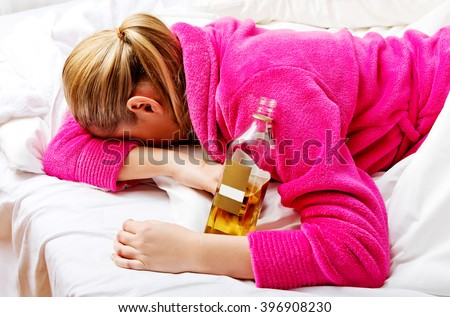 Young worried woman drinking alcohol in bed - stock photo