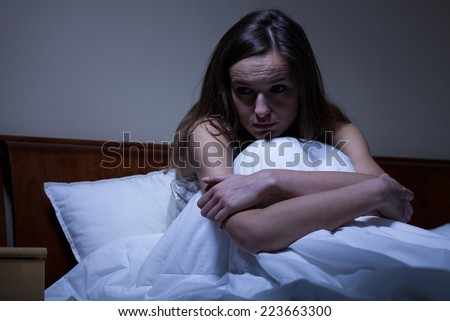 Young worried woman sitting in bed at night - stock photo