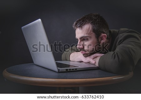 Young writer having a writer's block, feeling bored and uninspired in front of his computer