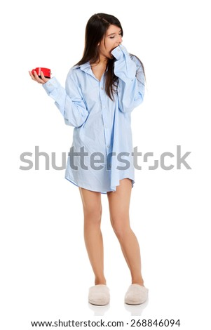 Young yawning woman in big shirt holding alarm clock. - stock photo