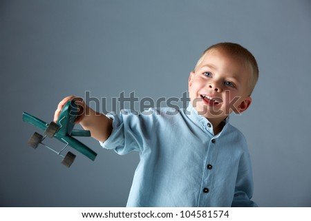young 3 year old boy wearing blue shirt playing with wooden toy airplane in his hand on blue studio background with space for text. - stock photo