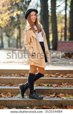 Young yet stylish. Soft focus portrait of a cute teen girl posing in autumn park outdoors  - stock photo