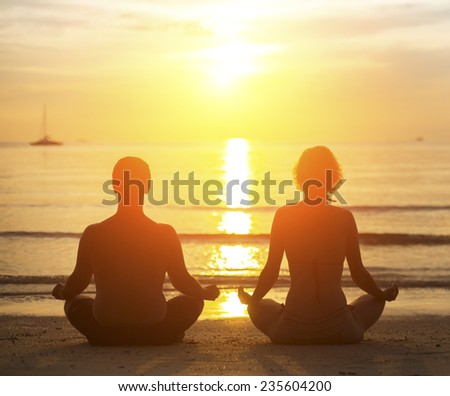 Young yoga couple meditating during amazing sunset on the beach. - stock photo