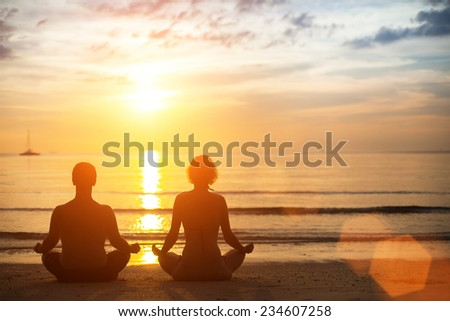 Young yoga couple meditating during amazing sunset on the ocean beach. - stock photo