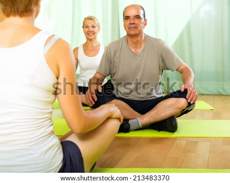 Young  yoga instructor showing asana to elderly attenders - stock photo